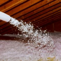 Spraying Blown Fiberglass Insulation for roof technician spraying foam insulation using plural component gun